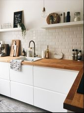 Kitchen with white cupboards and wooden …