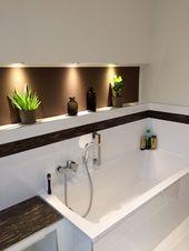 Badewanne mit braunen Farbakzenten und beleuchteter Wandnische