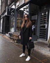 Schwarzes Manteloutfit mit weißen Turnschuhen