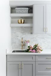 Laundry room designed with gray shaker cabinets, white quartz countertops and gr…