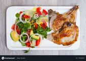 Delicious fried pork loin with healthy summer salad of tomatoes, avocado, grapef…