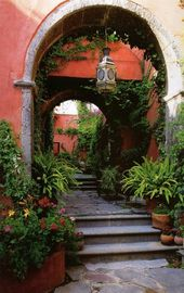 The bright spirit of Mexican design: Coral pink courtyard walls, stone arches, a…