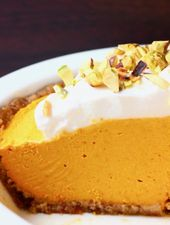 A white pie dish with no-bake pumpkin pie topped with whipped cream and chopped …