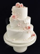 White and bush wedding cake with sugar flowers and royal icing detail.