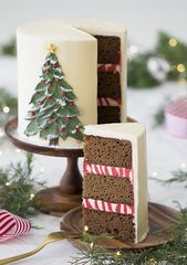 A photo of a gingerbread cake with a painted Christmas tree made from butter cre…