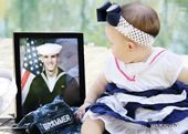Navy baby. 6 month pictures. Looking at dads boot camp picture!