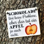 Schild mit Spruch SCHOKOLADE LÖST KEINE PROBLEME   – Apfel