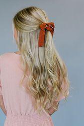 Halboffene blonde lange Haare, dunkelrote Schleife…