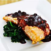 Blueberry Sauce over Grilled Salmon on fresh Spinich! I hope I don't spill any o…