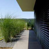 Minimalistische Gartengestaltung am Hang mit Wasserbecken aus Cortenstahl und Fe