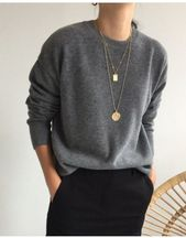 light gray slouchy sweater with crew neck and blac…