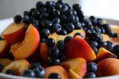 Geschnittene Pfirsiche mit Himbeeren, Blaubeeren und Schokoladenchips