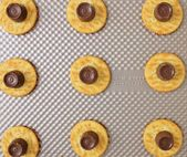 ritz crackers with rolo candy on top sitting on co…