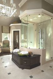 Stunning colors and lighting in this bathroom! Love how the shower is framed and the storage bench