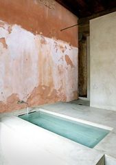 Exposed wall patina in modern bathroom design with…