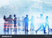 Silhouettes of business people shaking hands and communicating over blurred blue background with network hologram. Concept of technology in business. …
