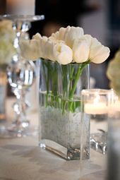 White tulips were arranged in a rectangular vase surrounded by floating candles