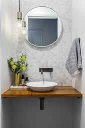 A modern powder room with marble look chevron tile…