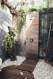 Holzboden und mit vielen kleinen weißen Steinen, ein Baum mit grünen Blättern