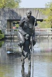 Survival of the Fattest is a sculpture of a small ravenous African man, carrying Girl Justice, an enormous overweight European girl who's an emblem of the wealthy world.