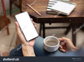 Mockup image blank white screen cell phone.men hand holding texting using mobile on desk at home office. background empty space for advertise text. co…