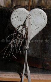 Herz aus Beton mit einem Satinband und einem klein…