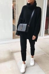 Women's Fashion Fall / Winter comfortable outfit with black pants, a long thick sweater with a black turtleneck and white sneakers