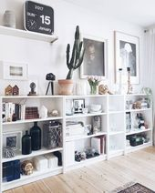 Living room shelf with gallery wall above and plants #storage