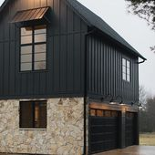 Black Moder Farmhouse with black board and batten siding, Flagstone stone accent