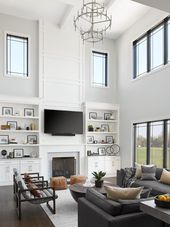 We flanked the fireplace with built-in cabinets and shelving, and carried paneling up the full double-height above the f...