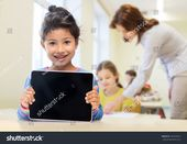 education, elementary school, technology, advertisement and children concept – little student girl showing blank black tablet pc computer screen over …