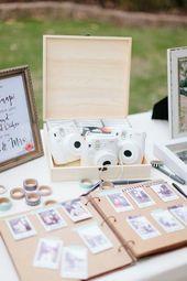Weiße Polaroidkameras sitzen auf einem Tisch über einem Schild im Buch, auf dem Gäste …