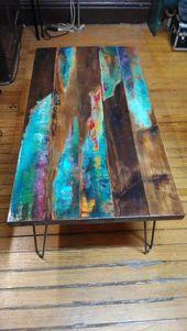 gemalter Kaffeetisch. Abstrakte Kunst auf beunruhigtem Holz. Industrierohrbeine