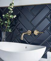 Dunkle Fischgrät-Badfliese mit Messingbeschlägen und weisser Spüle. Modernes Badezimmer mit schönen Kontrasten in Farben und Texturen.
