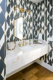 Clad in white, black, and gold geometric wallpaper…