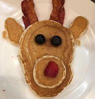 Rudolph Pancakes made from your pancake batter uses bacon for antlers, blueberries for eyes and a sliced strawberry for the nose!
