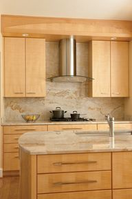 Vallon paired Tigers Eye maple cabinets with marble-like granite countertops.