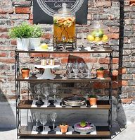 Bring the bar outside by using a bookshelf as a space to stash drinks, tableware, and service pieces.