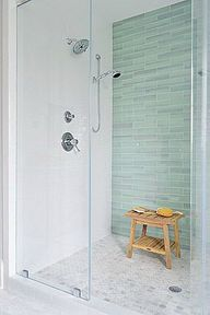 focal shower wall. Nice shower system. Teak bench. Shampoo storage?