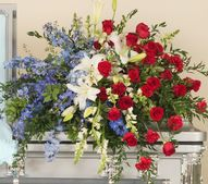 """Patriotic casket spray design featuring red roses, white lilies and blue delphinium.  Approximate Size for standard casket design is 40""""W x 15""""H.  Casket Spray, Patriotic, Red Roses, Lilies"""