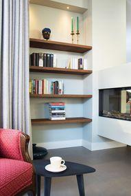 In deze grote woonkamer hebben we een haard haaks op een buitenmuur geplaatst en zo is er een gezellig leeshoekje gecreëerd. De zwevende boekenschappen zijn op maat gemaakt. Op alle muren zit een zachtgroene kleur.