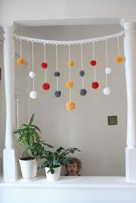 Hang hand made pom poms this year? Would just have to buy cheap yarn...and have a pom pom making party.