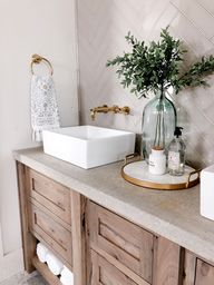 This DIY bathroom makeover was done by adding a concrete countertop over a rustic, wood vanity. It makes for the perfect mix of farmhouse, modern, and rustic stylings for a cozy, yet up-scale look. Our Kingston Brass vessel sink and wall mount gold faucet were the finishing touches. | Photo by @jettsetfarmhouse on Instagram | #modernfarmhouse #bathroomremodel #bathroomdesign #goldfaucet #rusticdesign #farmhousebathroom