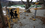 In this Monday, March 4, 2013 photo, a warning sign for drivers is seen beside a roadway, near a pile of radiation-contaminated soil at the Tsushima Junior High School in Namie, outside the the nuclear exclusion zone surrounding the crippled Fukushima Dai-ichi nuclear plant in Japan. Two years after a tsunami crippled the nuclear plant, towns surrounding it remain abandoned, too contaminated by radiation for residents to return for more than short visits. (AP Photo/Greg Baker)