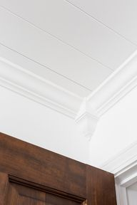 Corner of a ceiling with decorative crown molding and Armstrong WoodHaven Planks