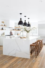 """White Kitchen.After installing the massive 12-foot island, Brooke knew the counters needed to be just as special. They opted for a Calcutta gold quartz for aesthetics and durability. """"To top it off, we did a waterfall edge so it would be the first thing you see when you walked into the house,"""" she explains.Since everything was white and light Brooke decided to add trendy elements with brass hardware and """"really fun"""" lighting. """"The high black contrast of the pendant lights"""