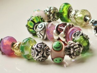 """Trollbeads (Danish: Troldekugler) is a Danish jewellery company with a worldwide distribution of its original jewellery concept.  Since 1976 the company has designed, produced and distributed small """"charms"""" to be worn on a bracelet or necklace, either separately or in combinations of multiple beads."""