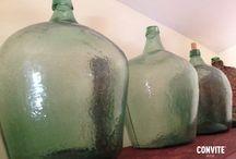 Damajuanas de vidrio y Cántaros de barro negro / La inspiración para nuestra botella. Antiguamente se dejaba reposar el mezcal en damajuanas de vidrio y cántaros de barro negro para conservar sus propiedades organolépticas.