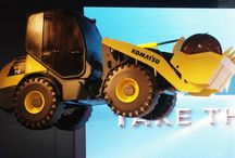 Backhoe Loader / For Komatsu, we constructed a free flying radio controlled backhoe loader that resembled the original in every detail. Our life sized model was then flown over the performers on stage at the product presentation.