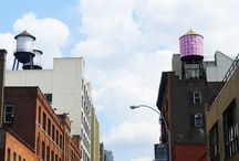 Look up! / The Water Tank Project's water tanks on the New York City skyline.